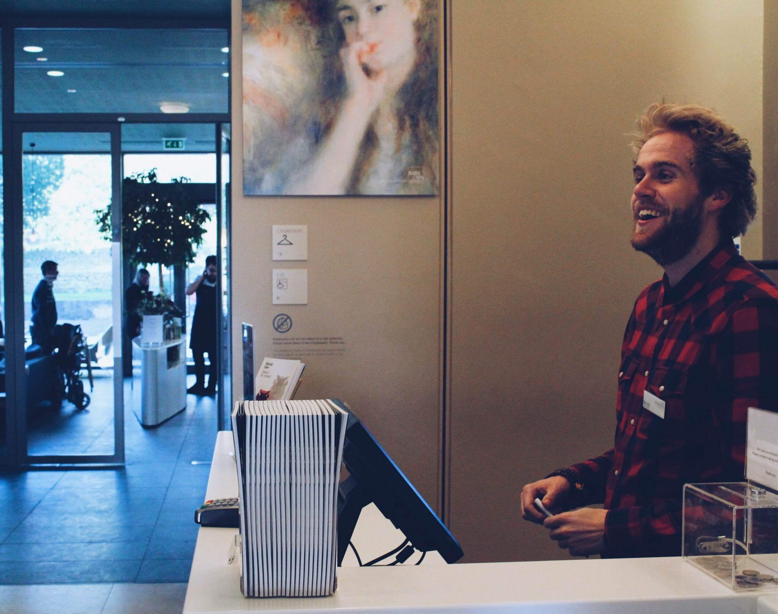 A volunteer smiling at the reception desk in The Holburne Museum
